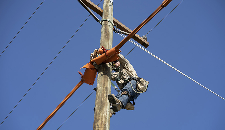 Lineman on Pole with Rubber Insulating Blankets and Cover-up